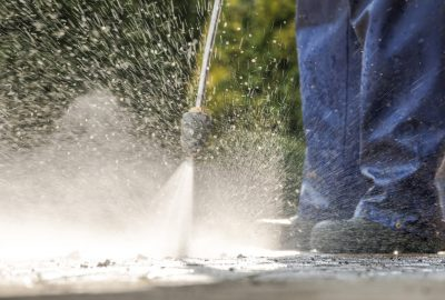 Pavement Power Cleaning. Pressure Washer in Action. Closeup Photo.